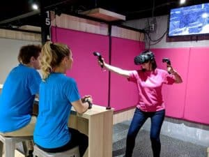 Woman playing in virtual Reality game room
